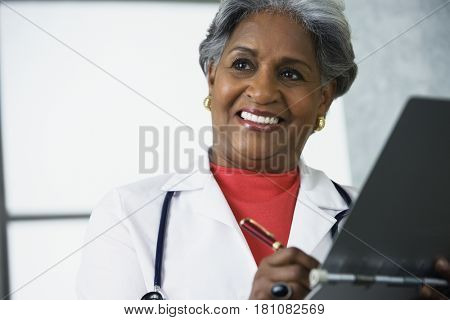 African female doctor writing in medical chart