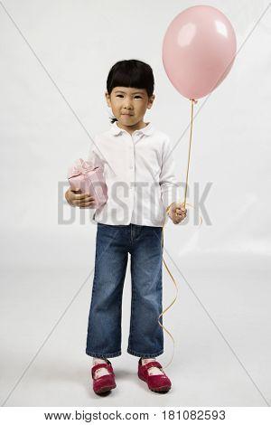 Korean girl holding balloon and birthday present