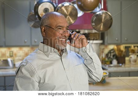 African man talking on cell phone in kitchen