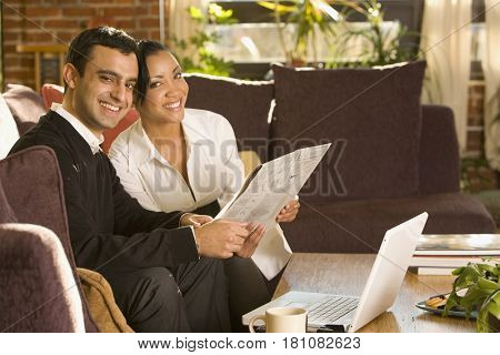 Mixed race couple reading newspaper in living room