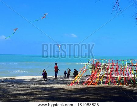People flying kites on the beach with rack of kites for sale on the right, Songkhla, Thailand