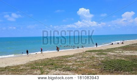 distant Muslim children playing and swimming at a Gulf of Thailand beach, Songkhla, Thailand