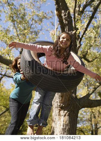 Hispanic grandmother pushing granddaughter on tire swing