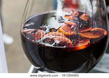 Making hot alcohol, mulled wine for sale at country fair. Glintwine from red wine with citrus and cloves in big glass. Closeup