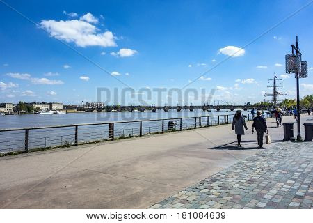 BORDEAUX FRANCE - APR 4 2017: unidentified People walking at the promenade of the River Garonne at Place de la Bourse in Bordeaux.