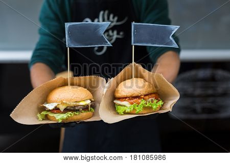 Fresh beef burgers cooked at barbecue outdoors. Cookout american bbq with text label. Big hamburgers with steak meat and vegetables closeup with chef unfocused at background. Street fast food.