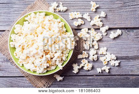 Salt popcorn on the wooden background . Top view
