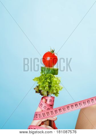 Woman Hand With Vegetarian Food And Measuring Tapes.