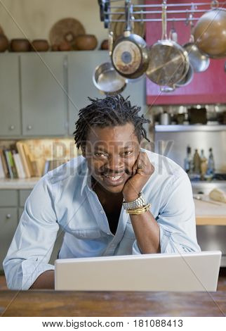 African man using laptop in kitchen