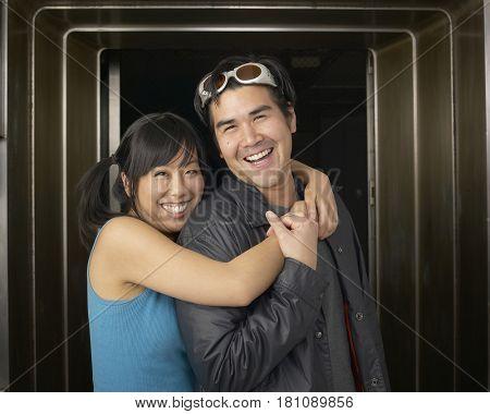 Multi-ethnic couple hugging in doorway