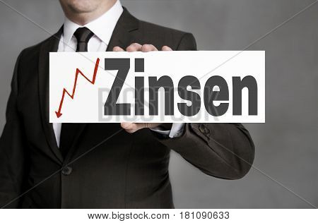 Zinsen (in German Interest) Sign Is Held By Businessman