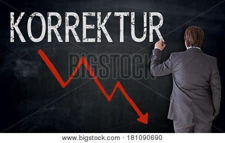 Businessman Writes Korrektur (in German Correction) On Blackboard Concept