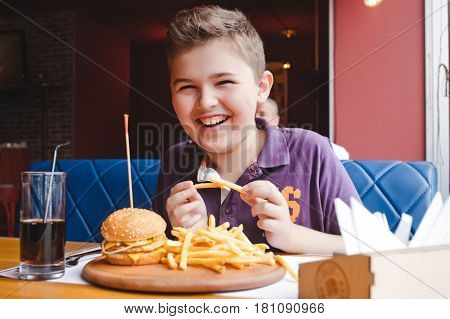 little boy eating a hamburger at a cafe, food concept