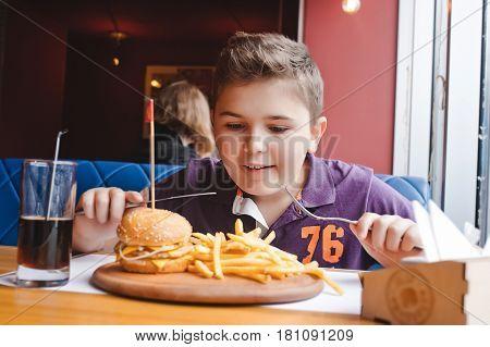 little boy eating a hamburger at a cafe, food concept