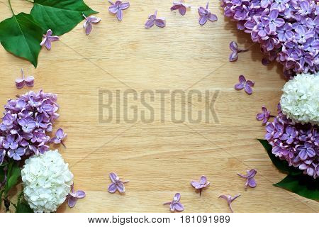 Spring floral background with fresh lilac flowers and leaves on a wooden background. Frame border with spring summer blossom. Copy space.
