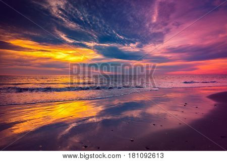 Waves and sramatic sunset with colorful clouds over sea at Glenelg Beach South Australia