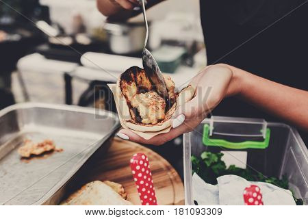 Fresh tacos. Selling mexican fast food. Female street vendor hands put fillings in taco outdoors. Snacks of commercial kitchen.