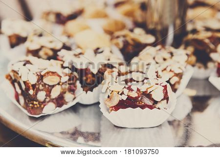 Caramel cakes on tray on banquet table. Pastry, caramel biscuits, cookies and candies closeup