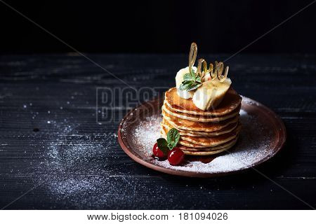 American pancakes on a plate with banana, cherry, mint, caramel syrop, love sign and sugar powder. Dark background.