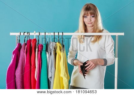 Pretty woman with empty wallet want clothing from wardrobe. Young undecided shopper girl spend all money for clothes. Shopaholic concept.