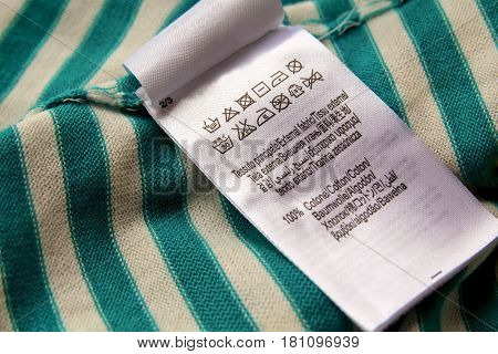 Clothing label with laundry care instructions symbols sign on cotton striped fabric background. With copy space.