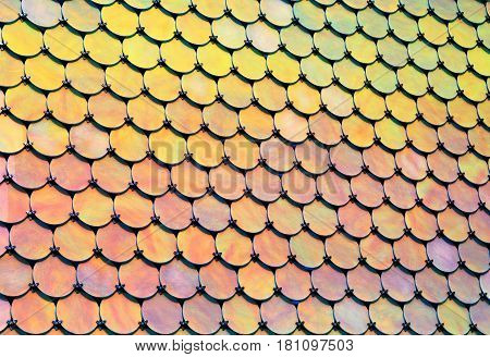Geometrical pattern of many round holographic iridescend metal plates. horizontal background of modern tile roof with perspective. Metallic abstract bright mosaic texture.