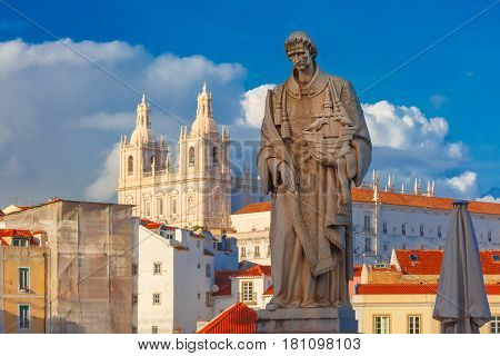 Statue of Saint Vincent, the patron saint of Lisbon, in Alfama, Lisbon, Portugal. Monastery of Sao Vicente de Fora on the background.