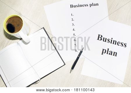 An inscription of the business plan, execution points, there is a notebook and a calculator next to it.