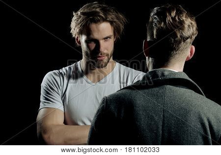 Two handsome men standing with faces opposite on black background. Male businessman in dark coat. Muscular macho unshaven caucasian in white tshirt with folded arms biceps triceps.