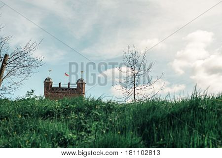 Watchtower of old dutch castle above grassy dike.