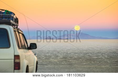 Full moon sunset with off road vehicle on Salar De Uyuni - World famous nature wonder place in Bolivia - Travel and wanderlust concept in South American exclusive landscape - Focus on infinity