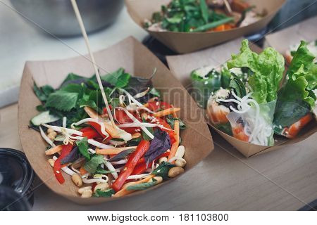 Street food, catering, restaurant delivery. Vegetable salads in kraft paper plates sold outdoors at local market place, close-up