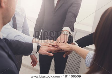 Multiethnic Team put hands together, connection, teambuilding and alliance concept. Crop of people in office, young businessmen and women unite hands for teamwork and cooperation.