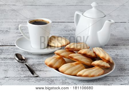 Classic french madeleines cookies on dish with coffee
