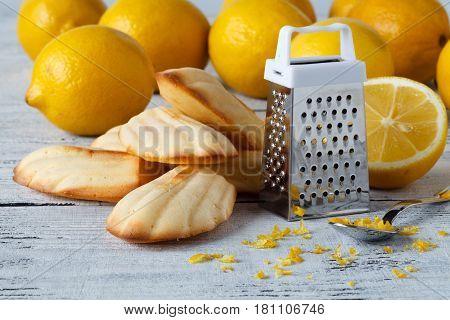 Lemon Madeleine cookies on white table with lemon zest