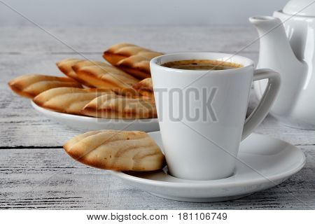 Madeleines cookies with coffee on white table