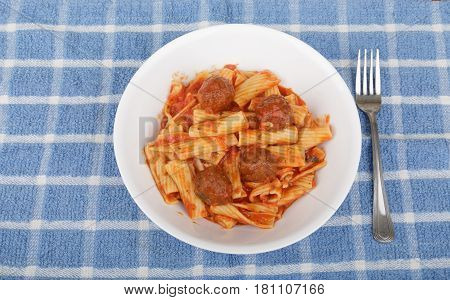 A bowl of penne pasta with tomato sauce and meatballs