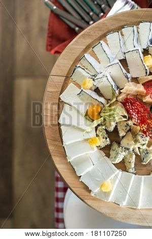 round wooden plate with different kinds of cheese honey. Top view. Brunch at an expensive restaurant. look from above