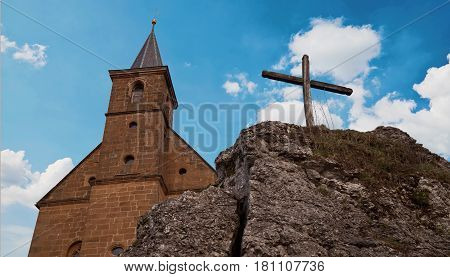 View on a church and a cross on a rock in front of a wonderful clouded sky - This is the church Guegel, Schesslitz, Germany