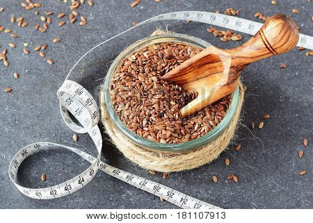 A glass bowl with flax seeds, olive wood scoop in it, with measuring tape on a grey abstract background. Healthy eating concept , dieting, beauty