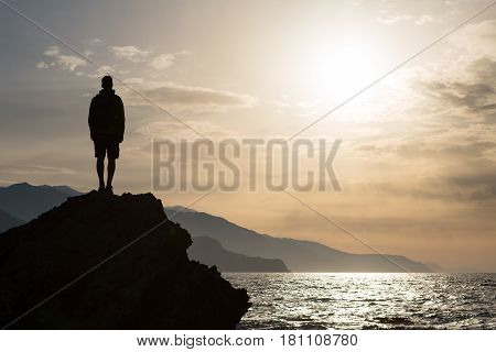 Hiker or runner silhouette backpacker man looking at inspirational ocean landscape and islands on mountain peak. Accomplished man celebrate beautiful sunrise and sea.Adventure and lifestyle concept.
