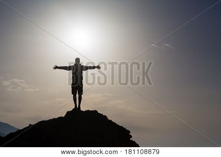 Man with arms outstretched celebrating or praying in beautiful inspiring mountains sunrise silhouette. Man hiking or climbing with hands up enjoy inspirational landscape on rocky top on Crete.