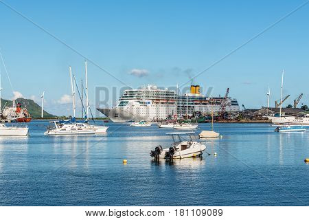 Victoria Mahe Island Seychelles - December 16 2015: Costa Neoromantica Cruise ship and boats in the foreground anchored in Victoria Harbour in Mahe Island Seychelles Indian Ocean Africa.