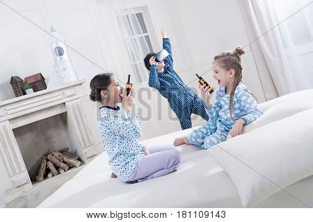 Adorable Little Kids In Pajamas Playing With Walkie-talkies And Virtual Reality Headset