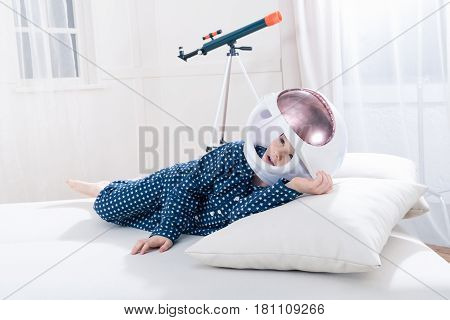 Cute Little Boy In Pajamas And Space Helmet Lying On Pillow