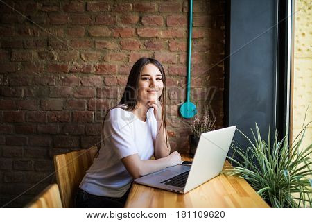 Side View Of A Young Woman Using Laptop In Cafe And Look At Camera