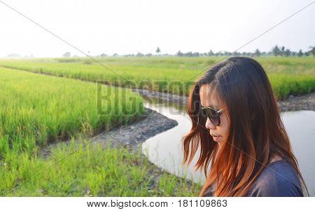 Asian woman wear sunglasses standing on paddy field in morning sunlight