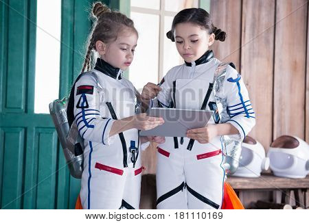 Girls In Astronaut Costumes With Jetpacks Using Digital Tablet