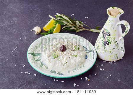 Homemade Greek traditional sauce tzatziki in a traditional colored bowl and a traditional jar with olive oil on a dark abstract background. Healthy eating concept. Mediterranean lifestyle
