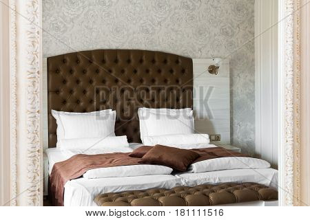 Luxury bedroom interior reflected in a mirror with a neat double bed with large brown upholstered headboard and a matching throw and ottoman at the foot in a classic room with patterned wall
